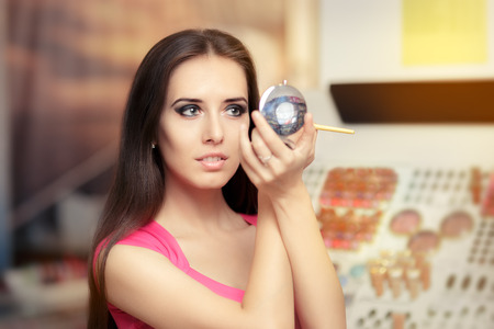 Beautiful Woman with Make-up Brush Looking in a Mirrorの写真素材