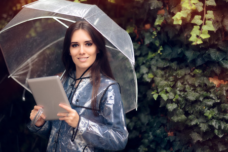 Smiling Woman with Raincoat and Umbrella Holding Pc Tablet