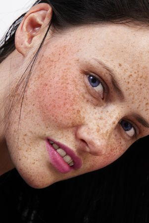 The face of a beautiful brunette woman with freckles on her skin, blue eyes and pink lips
