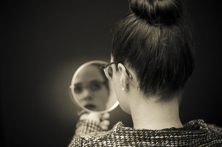 ego businesswoman looking in the mirror and reflecting