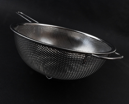 Stainless colander on black background