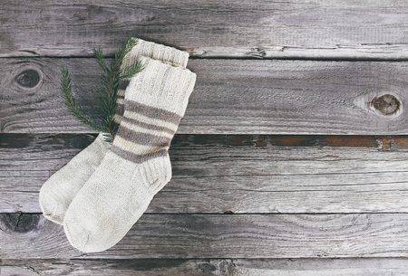 Photo pour Handmade warm knitted socks of wool yarn on wooden rough background. - image libre de droit