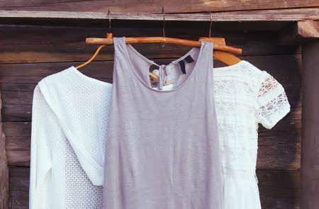 Photo pour Linen dresses hanging on a wooden hangers outdoors in summer day - image libre de droit