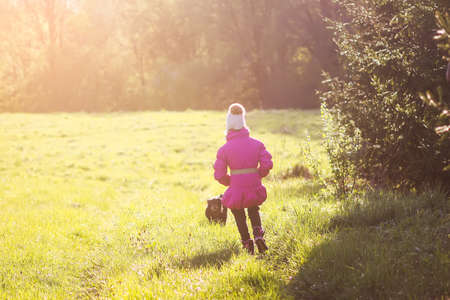 Photo pour Little girl walks with active black dog outdoors in spring sunny day. - image libre de droit