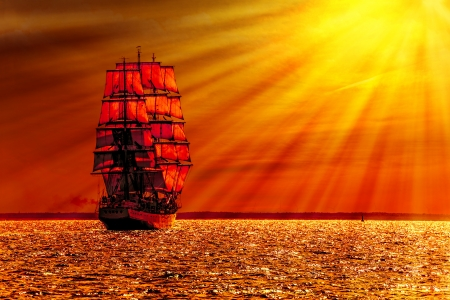 Sailing ship on the sea at sunset skyline