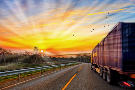 Photo pour Truck traveling on road at sunrise - speed and delivery concept. - image libre de droit