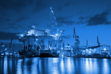Oil Rig at night in Shipyard industry concept.