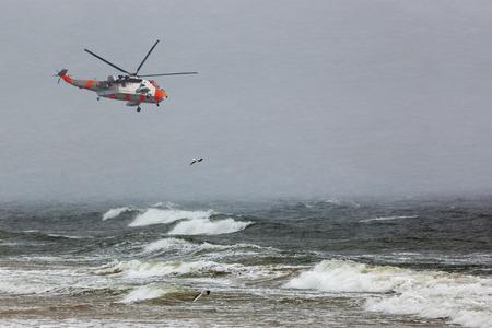 A helicopter rescue mission in difficult stormy weather at sea.