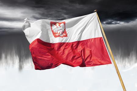 Polish national flag on dramatic sky.
