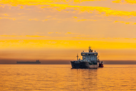 Tanker and tugboat on sea early morning just before sunrise.