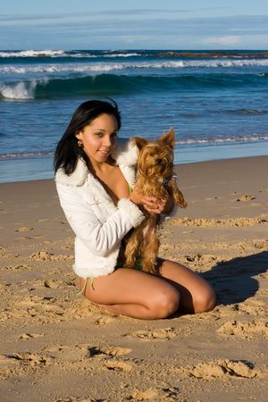 Beautiful model playing with a fluffy brown dog on the beach