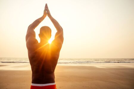 Foto für Man standing in yoga pose on ocean sunset paradise beach.Apollo athletic body, muscles - Lizenzfreies Bild
