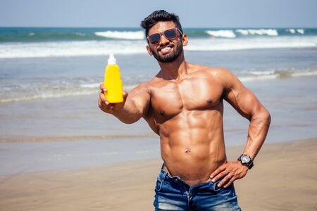 Photo pour happy young african man on the beach.Handsome and confident Masculine hard fitness bodybuilder with sixpack.India model male perfect abs, shoulders,biceps, triceps,chest holding a bottle of sunscreen - image libre de droit