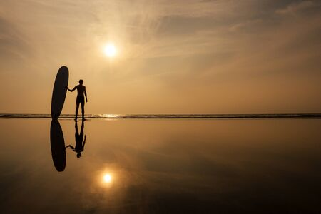 Photo pour A surfer man with his surfboard going to meet the sea waves evening sunset on the beach.male freelancer surfing on vacation in a tropical country paradise island. - image libre de droit