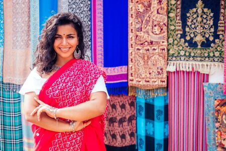 Photo pour business lady in red traditional sari and jewelery clothes shop owner cashmere yak wool shawls Delhi market.female seller in goa india arambol sale shop.designer seamstress tailor girl in Arambol Goa. - image libre de droit