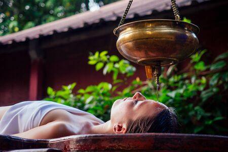 Photo pour ayurveda massage alternative healing therapy.beautiful caucasian female getting shirodhara treatment lying on a wooden table in India salon - image libre de droit