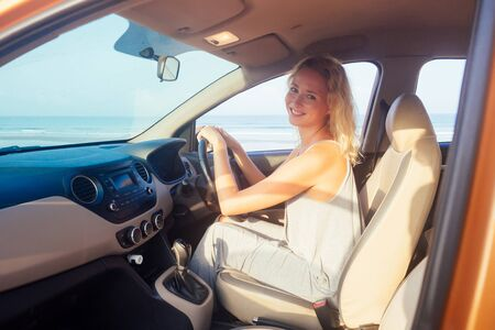 Photo pour blond business woman in gray dress driving in car on beacges - image libre de droit