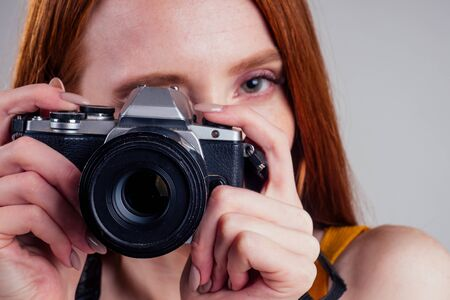 Photo for Photographer in a yellow shirt with her camera on white background studio. - Royalty Free Image