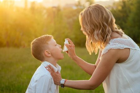 Photo pour caring mother uses an inhaler to her son in the park - image libre de droit