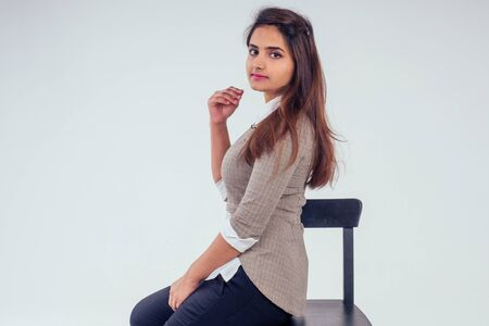 Photo pour beautuful indian woman wearing white shirt with collar and sweater with brown black hair in studio white background - image libre de droit