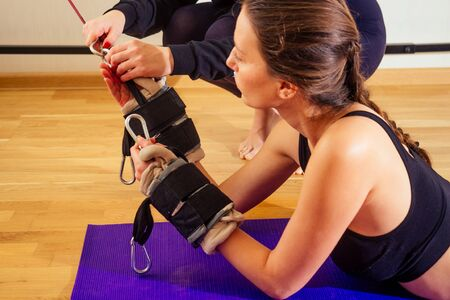 Sporty young caucasian woman doing stretching exercises of full body muscles workout on stretch aerobic aero strap in gym,yogi mat.