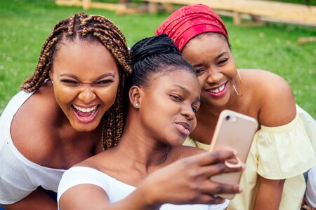 Photo pour portrait of three beautiful african-american women afro braids dreadlocks and turban taking pictures of yourself on the phone in the park at a picnic,sisters on vacation - image libre de droit