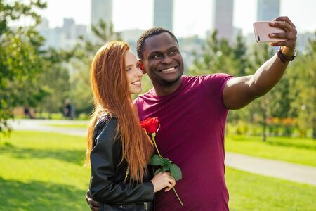 Photo pour Close up of interracial couple holding white rose in spring autumn park taking a selfie with a smart phone camera - image libre de droit
