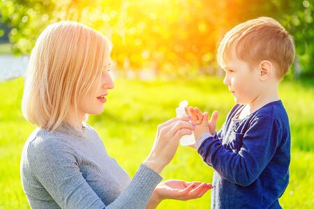 Photo for beautiful mother wipes her sons hands with wet hygienic napkins antibacterian sanitizer gel in the park in summer . anti bacterial napkins and freshness concept - Royalty Free Image