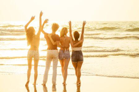 Foto de Happy friends partying on the beach with lemonade and beer . - Imagen libre de derechos