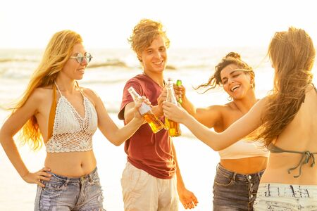 Photo pour happy international friends drinking smoothie juice from glass bottle on the beach - image libre de droit