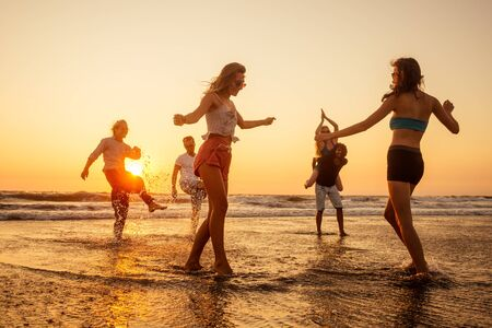 Photo for multicultural multinational happy people running into the sun carefree and happiness, vacation on sea. - Royalty Free Image