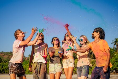 Photo for mixed race friends having fun with colors on seaside outdoors in Goa India - Royalty Free Image