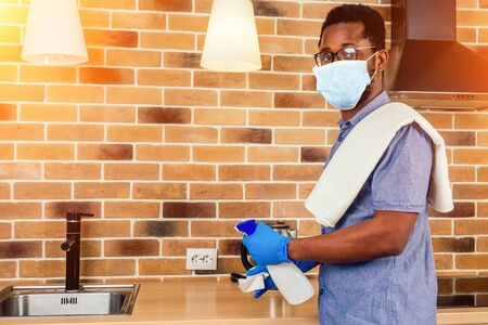 Photo pour african man in medical mask cleaning cooktop cooker hood at home ,Brick wall background - image libre de droit