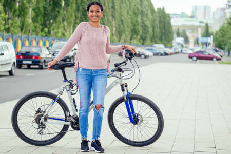 Photo for asian woman taking a a bicycle for a rent in downtown - Royalty Free Image