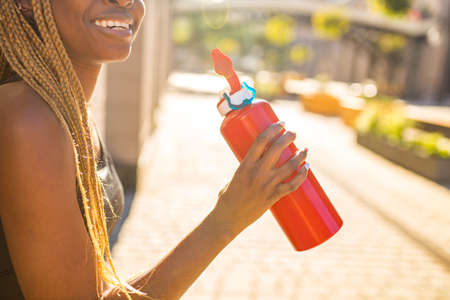 Photo pour african american woman drinking smoothies after jogging in the downtown streets - image libre de droit