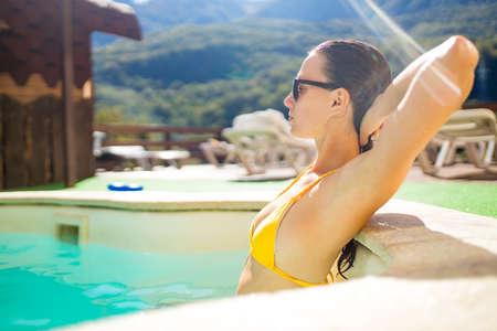Foto de woman in the pool looking at mountain landscape.Enjoying beautiful mountains - Imagen libre de derechos