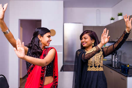 Photo pour happy indian sisters are dancing together in new light apartment with design repair moving concept house - image libre de droit