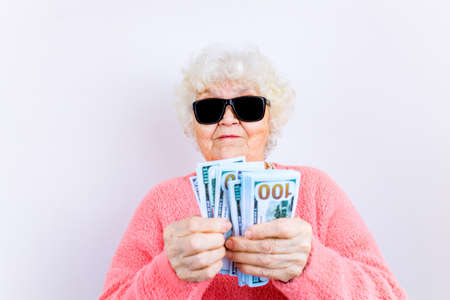 Photo for blonde old lady wear pinl sweater and sunglasses showing money isolated white background - Royalty Free Image