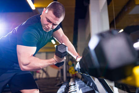 Photo for Fit and muscular man trains with dumbbells in gym - Royalty Free Image