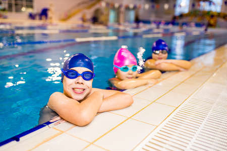 Foto de Disabled boys and girl with Down syndrome in swimming cap with goggles - Imagen libre de derechos