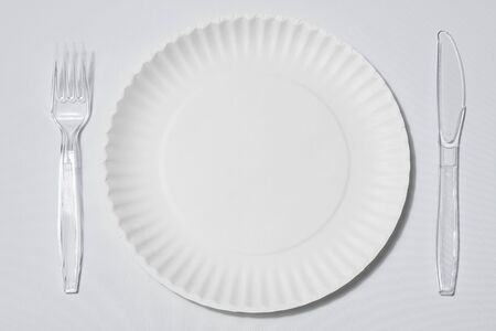 empty singleuse white paper plate with set of clear plastic fork and knife on white background or tablecloth