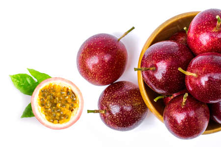 Photo pour Closeup passion fruit ( Maracuya ) in wooden bowl and cut in half slice with green leaves isolated on white background . Overhead view. Flat lay. - image libre de droit
