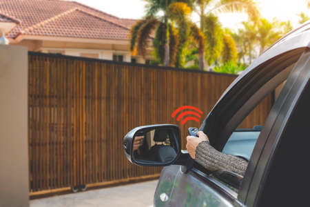 Foto de Woman in car, hand using remote control to open the auto gate when driving and arrive home. Automatic door, security system and wireless concept. - Imagen libre de derechos