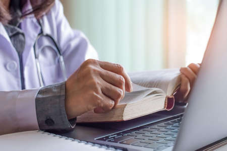 Female doctor in white lab coat concentrate on reading medical text book ,work on laptop computer with stethoscope and notebook on office desktop at hospital or clinic.