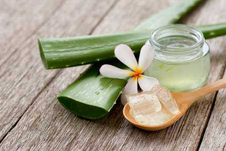 Photo pour Aloevera gel with cactus green leaf and plumeria flower on wood table background. - image libre de droit