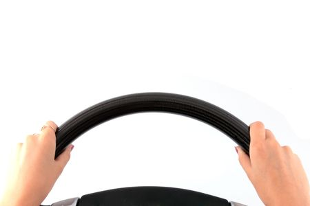 Female hands on a steering wheel on the isolated white background