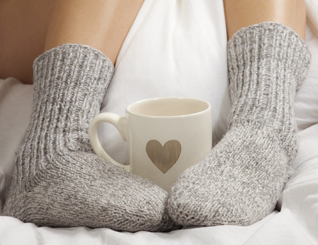A cup of coffee or hot chocolate and female feet with socks on a white sheets