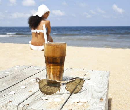Iced coffee and glasses on a wooden table on the beach. In the distance woman in swinsuit and hat watching the sea.