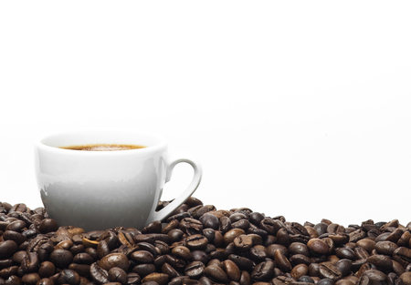 White coffee cup and coffee beans isolated on a white background.