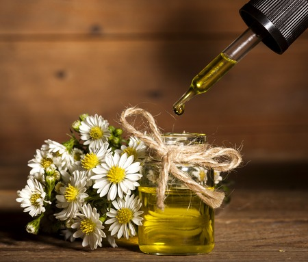 Chamomile essential oil and bouquet of chamomile flowers on wooden background